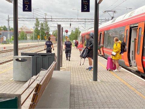 To politiansatte er på vei mot enden av toget for å bistå Vy med en vanskelig passasjer.