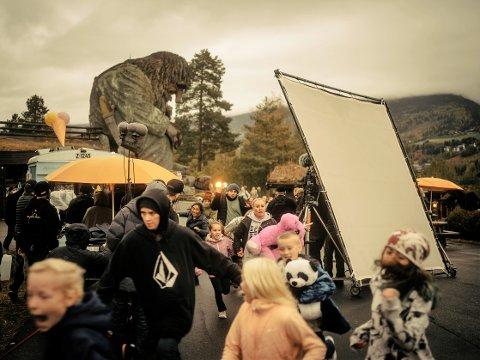 TROLLBESØK: Et digert troll tramper inn i Hunderfossen Familiepark og skaper panikk blant de besøkende. Det er trolig en av scenene vi får se når filmen Troll har premiere i 2022. Her fra torsdagens innspilling på Hunderfossen. SVEIP.