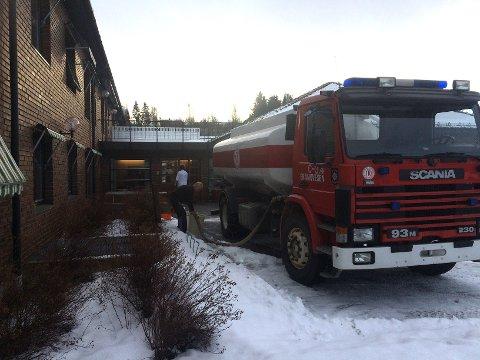 Tankbilen til brannvesenet står parkert utenfor sykehjemmet slik at det er mulig for de ansatte å få tak i noe vann.