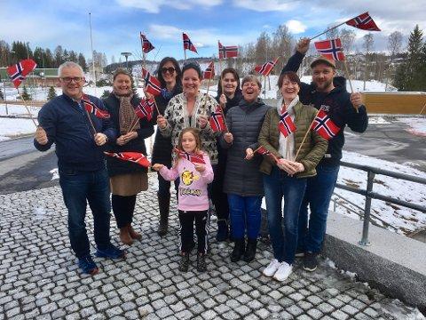 Første 17. mai på ny skole: Petter Dahl som representerer Brandbu skolekorps og Moen musikkforening, Berthe Hvinden Alm fra 17. mai-komiteen, FAU-leder Anne Hagen Grimsrud, Bente Nari Nymoen som er leder av 17. mai-komiteen, Merete Hoffsbakken Melbostad, Anne Berit Rækken, Trine Holme og Frode Myrdal, alle fra 17. mai-komiteen og Juli Marie Nymoen-Heggen (foran), ønsker alle velkommen til stor 17. maifeiring ved Brandbu barneskole. I år starter toget fra barneskolen og ender opp ved det gamle gymnaset og videre inn i Størenslunden som vi ser i bakgrunnen.