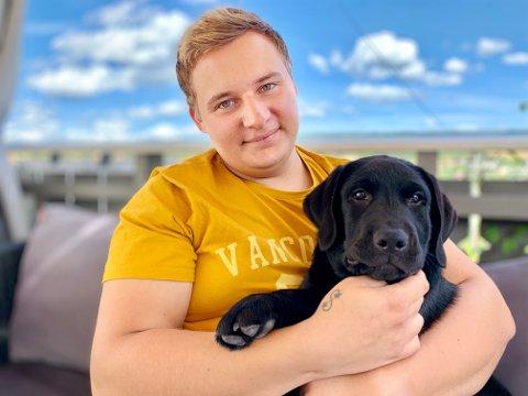 VIL HA MER: Christoffer Wæhler Jansen (24) ønsker seg full jobb, selv om det akkurat nå også er ganske mye jobb med labrador-valpen Odin.