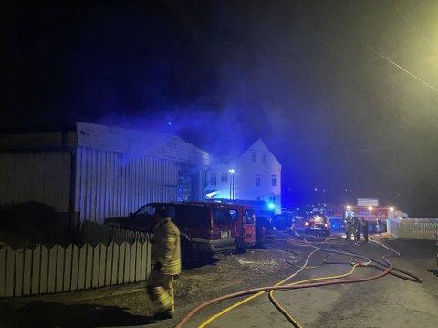 Flere biler står parkert langs bygningen det brenner i.
