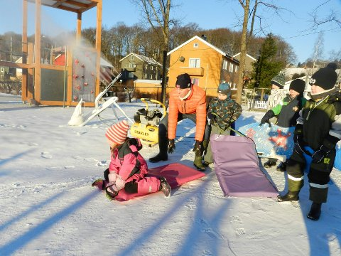 Snøkanonen ved Høvleriet barnehage sørger for akeføre. Her aker Stella Kopp Kleiven og Lorik Kajtazi. Jan Martin Engum i blått til høyre. Styrer Tomas Andresen hjelper til.