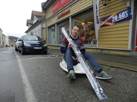 TAR DET HUMORISTISK: Daglig leder Atle Simonsen på akebrett og med ski over skuldra på svart asfalt. Ikke mye som minner om vinterføre her, nei.