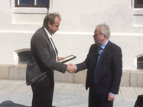 FYSISK BEVIS: Riksantikvar Jørn Holme overrekker fredningsbeviset til Ole Kristian Sørlie. Dermed er Sørlie eier av et fredet fengsel og en fredet politistasjon.