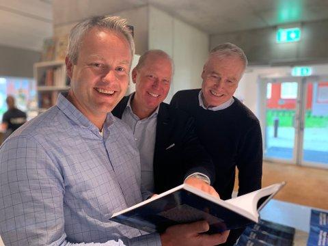 SPENNENDE HISTORIE: Direktør for strategi og forretningsutvikling Martin Vatne,direktør for krafthandel Morten Karlsen og prosjektleder for varme Egil Erstad blar ihistorieboken.