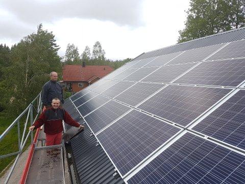 NYINSTALLERT: Torgal Ståhl (i bakgrunnen) på taket, der hans nye solcelleanlegg har blitt installert. Foran står ektemannen Anders Samuelsen.