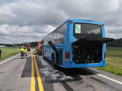 MÅTTE SLUKKES: Brannvesenet fikk kontroll over røkutviklingen i bussen, og den blir mandag ettermiddag tauet bort slik at trafikken kan passere stedet i begge løp.