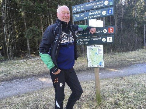 JUBILANT: Jan Gunnar Lilledal står ved løypeskiltet på Ertemoen, inngangsporten til Ertemarka der han har lagt ned mange trenings- og dugnadstimer. Nå runder han 70 år. Foto: Tille Andreassen