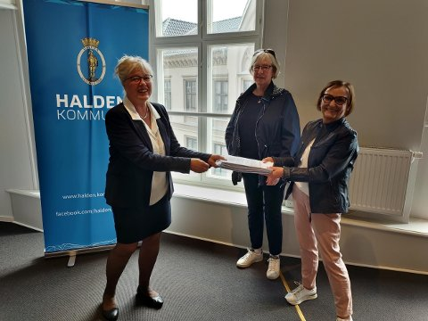 Ordfører Anne-Kari Holm får underskriftene fra borettslagsleder Eli K. Andreassen.