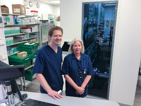 ROBOTROM: Bak noen vegger og en glassdør står roboten. Foran står sykehusapoteker Knut Raanaa og tekniker Hanne Engen.