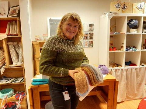 Mona Østerbø med to håndfuller votter som er til salgs i husflidsbua.