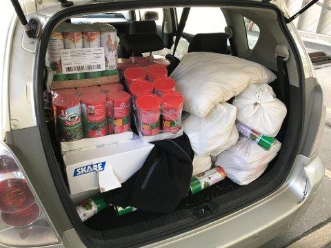 Bagasjerommet på bilen var fullasta med mat. Både posane og pappøskjene er fulle av kjøt.