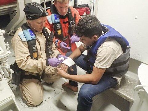 SKADE: Tordis Kristin Bjorland gir her førstehjelp til en mann som ble tatt om bord med knivskader i hånda. Bak sitter Andreas Johansen fra Redningsselskapet.Alle FOTO:  Redningsselskapet