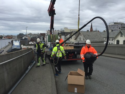 MONTERING: 18 nye lysstolper blir nå satt opp på Risøybrua. Bjarne Tollefsen (fremst) fra Aibel er blant arbeidsfolkene om monterer belysningen.