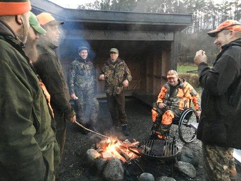EN AV GUTTA: Leif Arilf Fjellheim koser seg ved bålet sammen med jaktlaget.