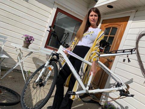 Linn Kristin Sørvik viser fram sykkelen som ble fullstendig ramponert av guttegjengen.