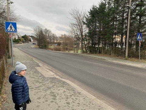 BORTE: De hvite stripene i Salhusvegen nord for kirkegården er borte, og har vært det lenge. Peder Sigurd Lindøe og andre barn opplever at bilene ikke stopper for dem lenger.
