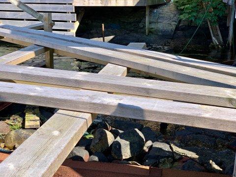 BRYGGESJAU: Den påbygde bryggen over den gamle steinbryggen det strides om. Merket i berget (øverst i bildet) markerer den nye grensen.