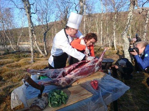 Svein Jæger Hansen er Norges fremste villmarkskokk. Her instruerer han landbruks og matminister Olaug Bollestad i skjæring av reinslakt.