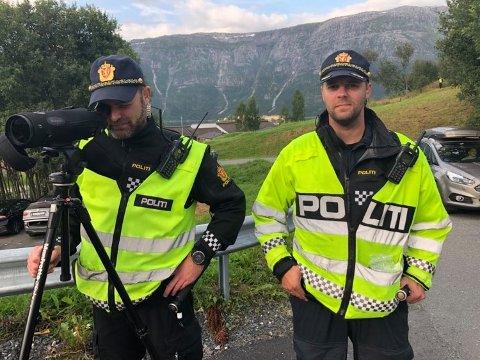 KIKKERT: Jostein Rørvik (t.h.) og kollega Sven Henning Kvernø sjekket om bilistene brukte bilbelte. I bakken bak de to betjentene sto ytterligere to politifolk og målte fart med en lasermåler (vi skimter så vidt den ene, i gul vest oppe t.h.). I midten bak i bildet ser vi taket på Kulstad skole.