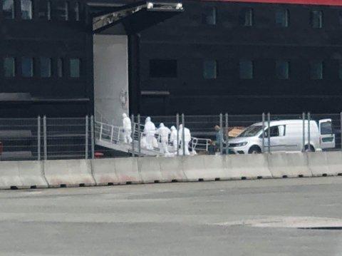 GÅR OM BORD: Personell iført fullt smittevernutstyr går om bord på MS Roald Amudsen sent onsdag ettermiddag.