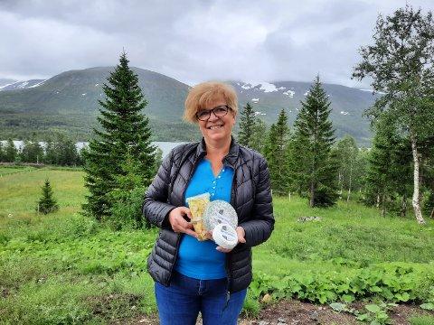 Siri Stabbforsmo står med favnen full av ost. Bak henne ligger Børgefjell og foran ruver Bæråsen og i midten ligger Strandli gård.