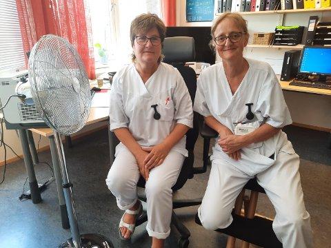 VIFTE: Først nå fikk hjelpepleier Monika Smedseng (til venstre) og  teamleder  Mona Aas, vifte  på kontoret. - Men vi må lukke døra og vinduene når vi alle samles til rapportmøter. Da blafrer papirene utover gulvet, og det blir steinhett inne på kontoret, sier de to. Men tankene deres går mest til pasientene som lider.