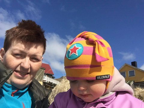 FERIE: - Vi er mange som trenger å vite at vi får bilene med ut til øyene i Måsøy, sier Brita Hansen med barnebarnet Fie Emilie i sola på Rolvsøy.