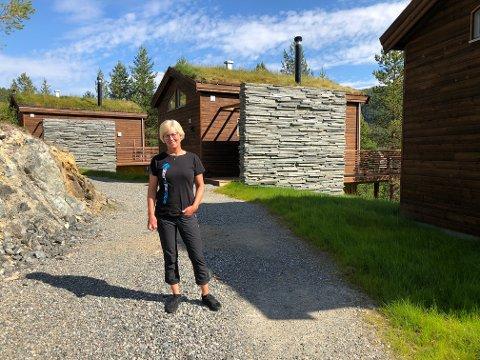 BJØRNFJELL: Synnøve Opgård Andersen viser stolt frem de nye hyttene på anlegget.