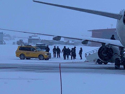 Her føres en person ut av flyet og inn i en ventende politibil.