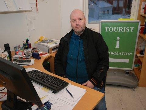 LEVER I SPENNING: Daglig leder Oddbjørn Hansen for Gamvik frivilligsentral vet ikke om han har jobb fra årsskiftet. Skiltet i bakgrunnen forteller om én av mange oppgaver sentralen har.