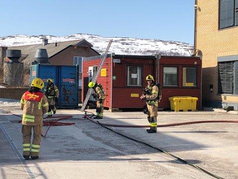 SLUKKET: Brannvesenet er i gang med å rydde opp etter å ha slukket en mindre brann utenfor politihuset i Kirkenes.