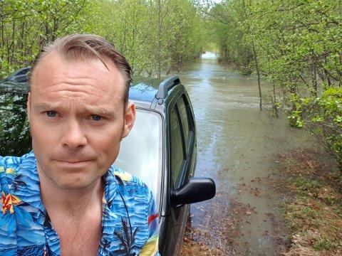 «VANNFAST»: Børge Eieland og familien kommer seg ingen vei med familiens biler. Opp til bilene, er det godt med vann, og i tillegg er da også Klemetstadveien stengt på grunn av ras et annet sted langs kjøreruten.