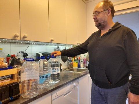 VANN PÅ FLASKE: Tore Lyder Johnsen (59) viser fram vanndunkene som er drukket siden helgen. Han håper problemet med jordsmak snart går over.