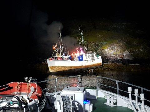 I FLAMMER: Her ser vi fiskebåten i flammer og liggende i fjærasteinene.