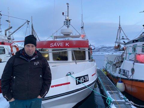 VIL HA MOLO: Fisker og reineier Jon Olav Guttorm ved båten sin Sáve K ved kai i Torhop. I mellom båtene (til høyre) skimter en bølgebrytere som skal sørge for lunere liggeforhold. Det er der det er tenkt etablert en molo, som vil gi enda bedre liggeforhold for den største fiskeflåten innerst i Tanafjorden.