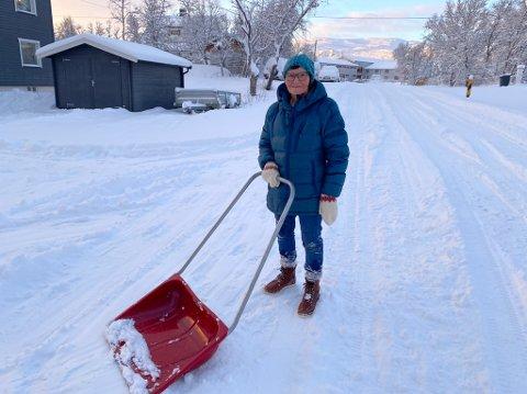 FORNØYD: Endelig kom snøen, sier Sigdis Olsen mens hun måker hele gårdsplassen.