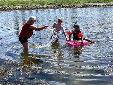 I VANNET: Bjørg Holmen og barnebarna Peder Holmen Sørli og Emeli Holmen testet badevannet på Røstad onsdag. Varmere skal det bli!