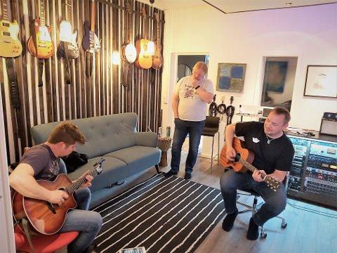 Knut Børge Edvardsen hører på mens Roger Karlsen og Vegar Myrstad idemyldrer rundt gitarriff.