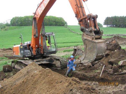 Tor Haugstad er med i arbeidet hjemme på Fuglestad. I gravemaskinen sitter Jon Ove Årsland som har gjort det meste av gravearbeidet på anlegget.