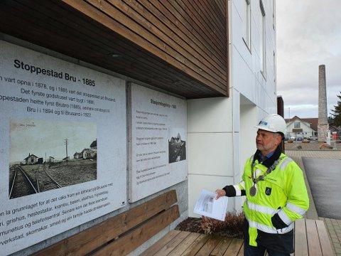 HISTORIKK: Hå-ordfører Jonas Skrettingland leser om Brusands historie på ytterveggen til den første boligblokka i sentrum. Det vil også komme flere slike digre tavler som skal festes på blokka som nå skal reises og stå ferdig i 2022.