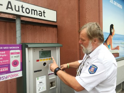 FIKSER: Trafikkbetjent Kjetil Halvorsen setter automaten i stand igjen. Årsaken til problemet er unektelig noe kuriøs.