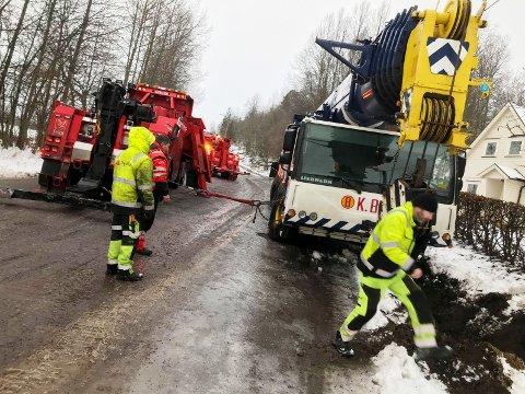 SKLED: En mobilkran på 60-tonn skled av Kleivanveien tirsdag morgen. Den måtte ha hjelp av to store bergingsvogner for å komme opp av grøfta. Arbeidet førte til at Kleivanveien ble stengt.