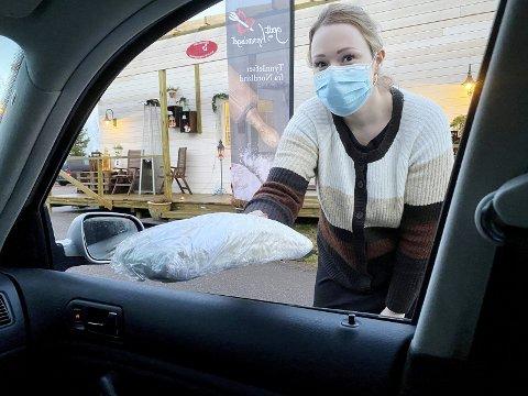 «Drive-in lefser» på Barstad: Malen Hagen lever tynnlefser gjennom bilvinduet etter bestilling over telefon. – Noen har valgt å kjøpe fra bilsetet, sier hun. Foto: Pål Nordby