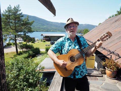 """Fred Erland Nordseth tar en trall på sin veranda, med Eikeren i bakgrunnen. – Som ungdom var jeg som ungdom flest. Vi turet rundt på motorsykkel med telt og soveposer. Det var festing, øldrikking og herrens glade dager. Som 12-åring begynte Fred å spille gitar. Etter noen år spilte han såpass bra at han kunne hive gitaren over skuldra og dra på festligheter med sang og musikk. Senere ble det gitar og sang i bandene """"Eidsfoss Hjærneverk"""" og «Vise Menn»."""