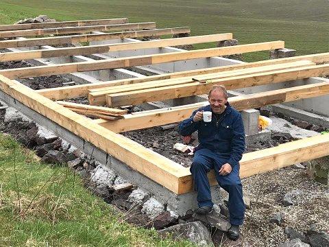 FORTJENT PAUSE: John Olafsen sitter på grunnmuren av lemmelåven, med noen av gulvbjelkene på plass.