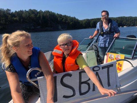 IS PÅ SJØEN– Det er veldig moro, sier Nikolai Sanskro (9) i det han rekker ut en saftis til en av båtturistene. Med på båten i helgen var mamma Monika Sanskro og Sverre Zachariassen. Det er første året de forsøker seg på trenden etter å ha sett to jenter som gjorde det samme i fjor.