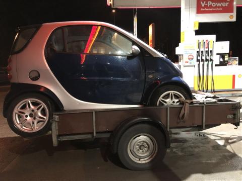 FARLIG LAST: Med dårlig strammede lastestropper og bakhjulene stikkende ut på baksiden fraktet den godt voksne mannen denne Smart-bilen med personbil og tilhenger. Foto: Politiet