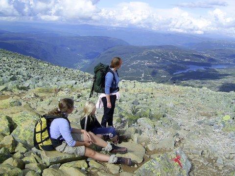 Gaustatoppen: Jenter sitter og ser på utsikten. Ungdom i naturen. På fjelltur.